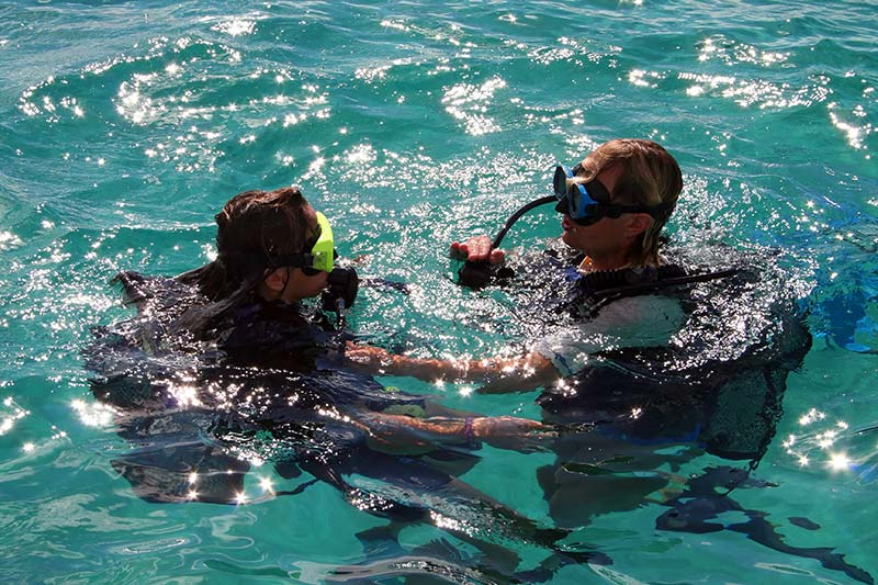 A Dive Provo instructor shows a rescue diver how to calm someone on the surface